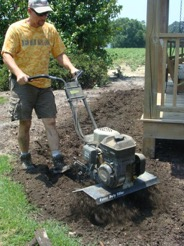 Marshall Warren is tilling the soil for preparation of planting.