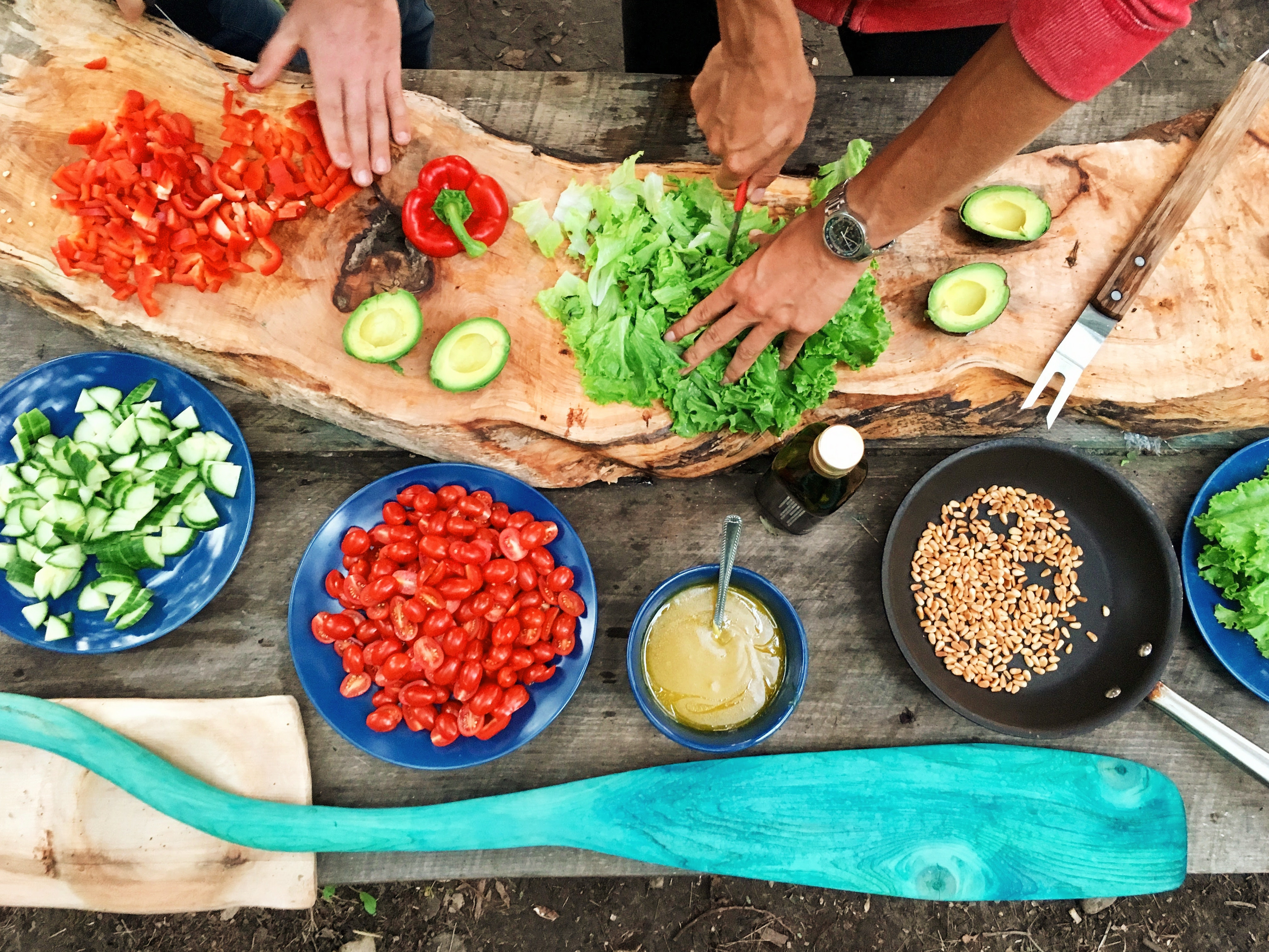 aerial picture of of lettuce being cut up, red bell peppers being cut by another person, a barbecue fork beside the lettuce, indigo blue bowls filled with already cut cucumbers, cherry tomatoes, some type of yellow dressing with a spoon in it, and a black bowl with seeds, also on the cutting board is cut avocado without pits. The cutting board is made of a unique piece of wood or stone, and for visual interests, there is a teal colored wooden paddle at the bottom of the indigo bowls