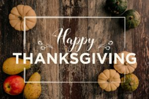 Happy Thanksgiving wrote in white letters with rustic wood background and small pumpkins in corners of picture