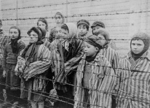 black and white photo of children standing in a concentration camp during the Holocaust era