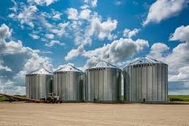 4 grain bins with blue sky and white clouds