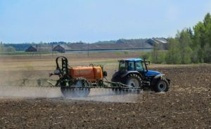 tractor spraying disked field with pesticides